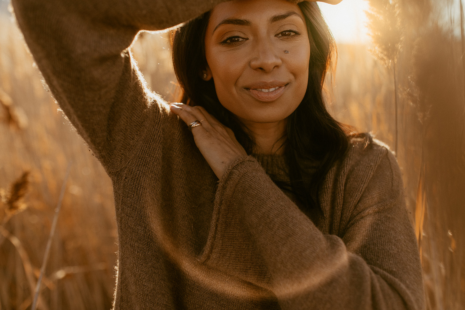 A portrait photo of a woman who stands in a cornfield while the sun shines.