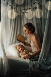 A woman is reading a nighttime story to her little one lying in bed.