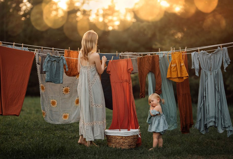 A woman is hanging up laundry in her garden with her little girl standing right next to her.