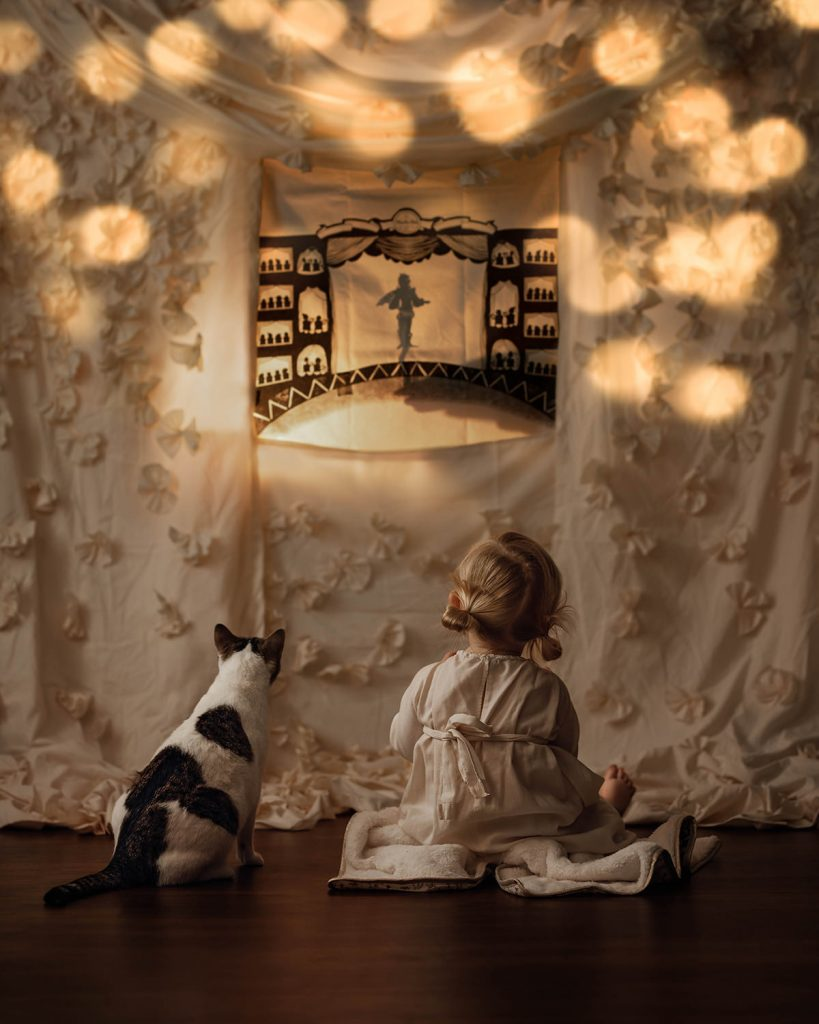 A little girl and her cat are sitting in front of a wall with a blanket hanging in front of it that shows a theatre scene.