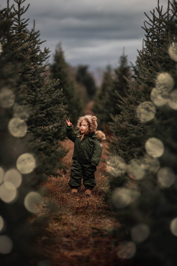 A little child is standing next to smaller trees.