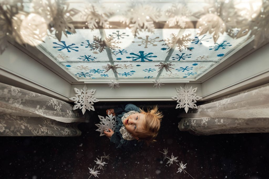 A little girl is standing next to a window and looking up to the paper snowflakes hanging from the ceiling.