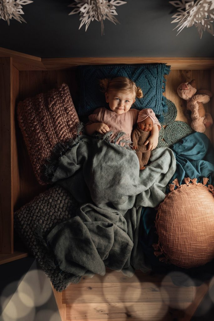 A little girl is lying in bed and holding her doll.