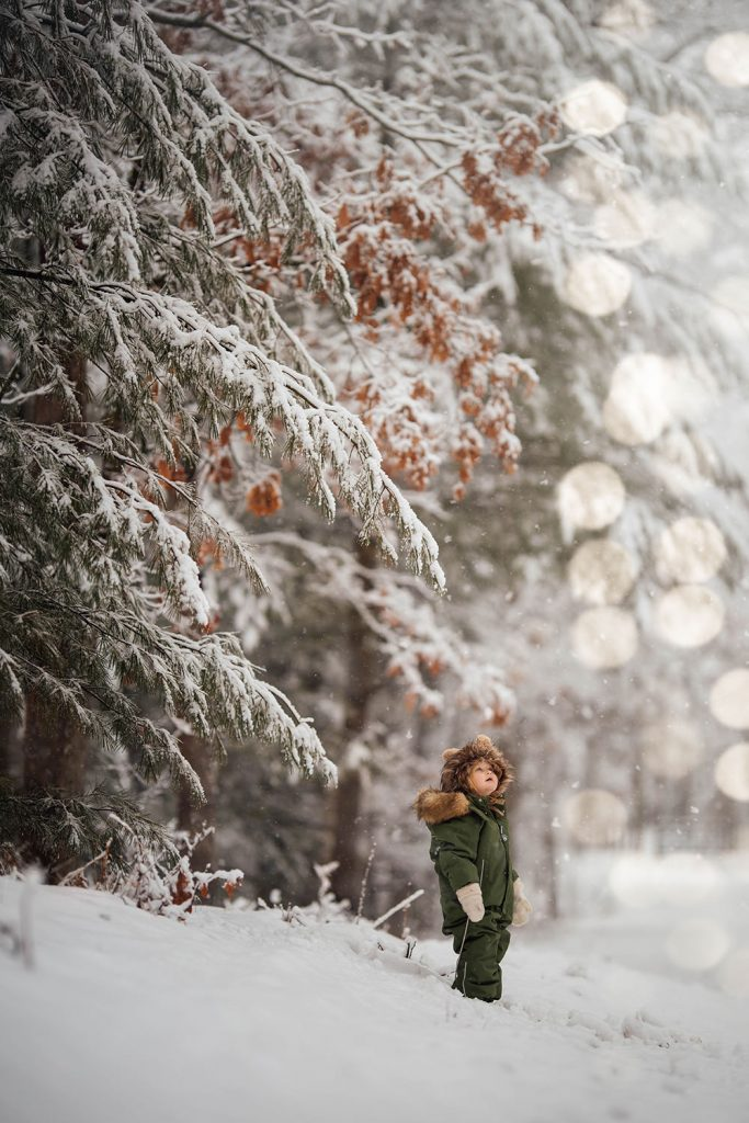 A little child is standing outside in the snow and looking towards the sky, with the forest right next to him or her.