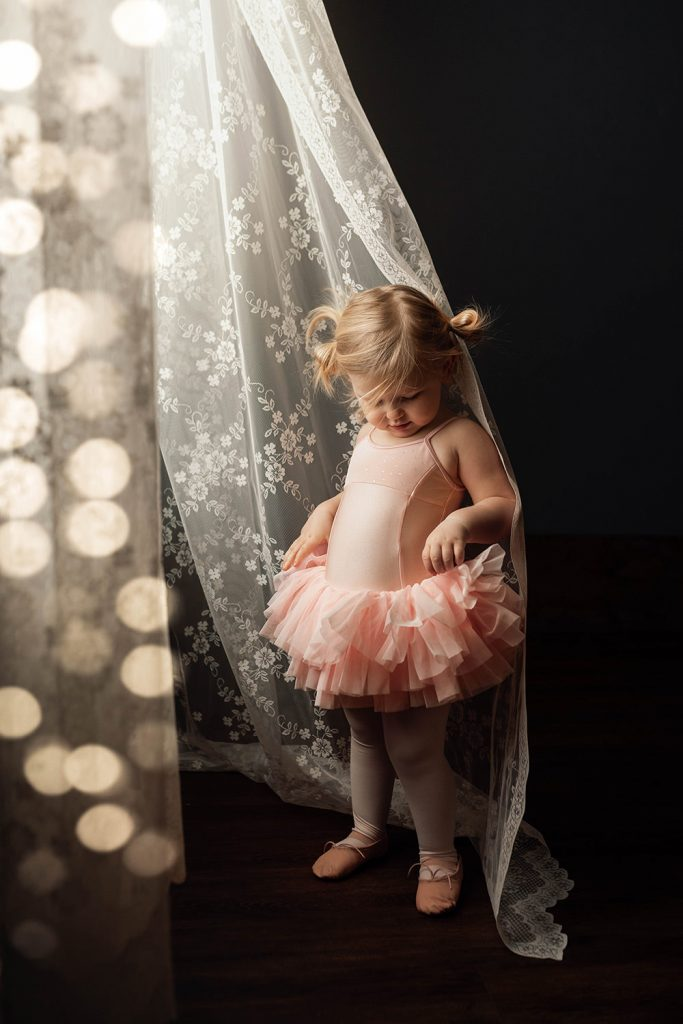 A little girl is wearing a tutu and standing next to a white curtain.