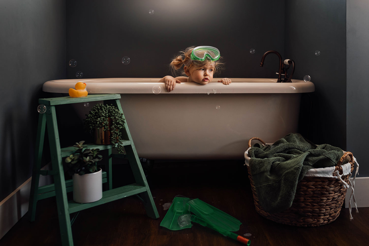 A little girl is sitting in a bathtub and wearing goggles.