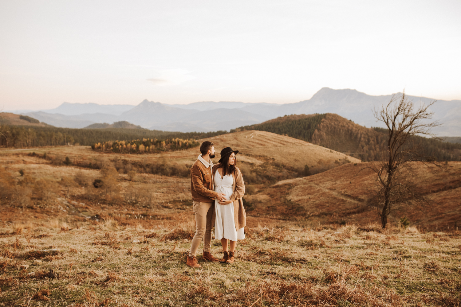 A photo of a man and a pregnant woman who stand on a small hill and look in the distance.