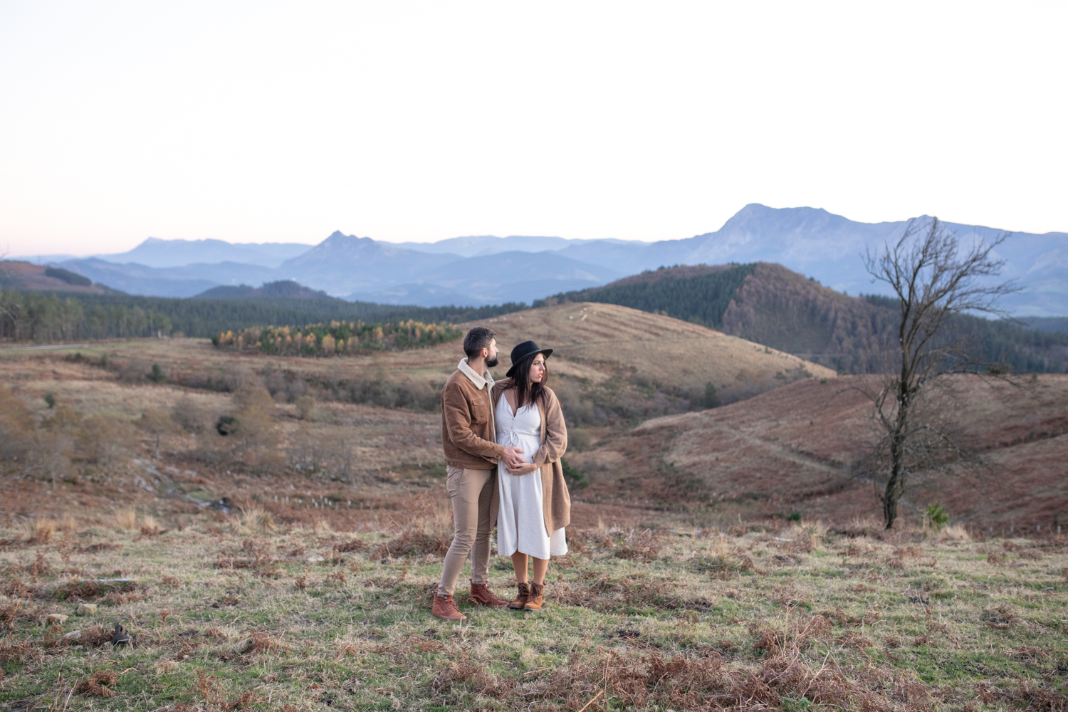 An unedited photo of a man and a pregnant woman who stand on a small hill and look in the distance.