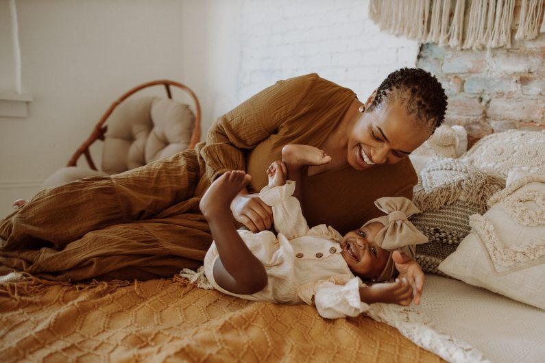 Mother and baby playing on a bed while laughing