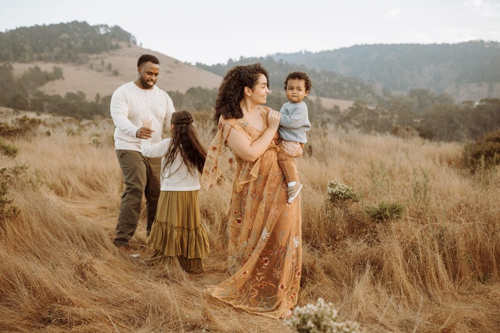 A picture of a family with two kids that walk through a field.