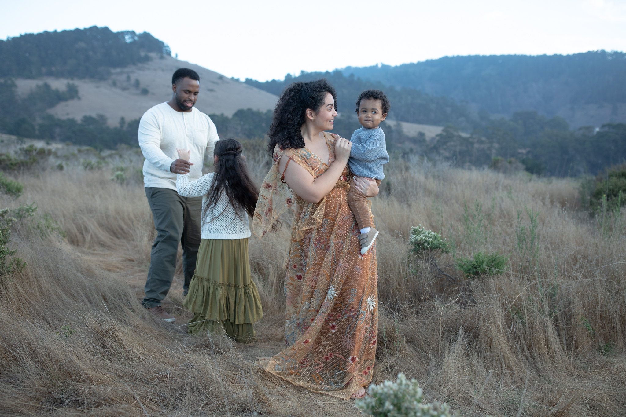 An unedited picture of a family with two kids that walk through a field.