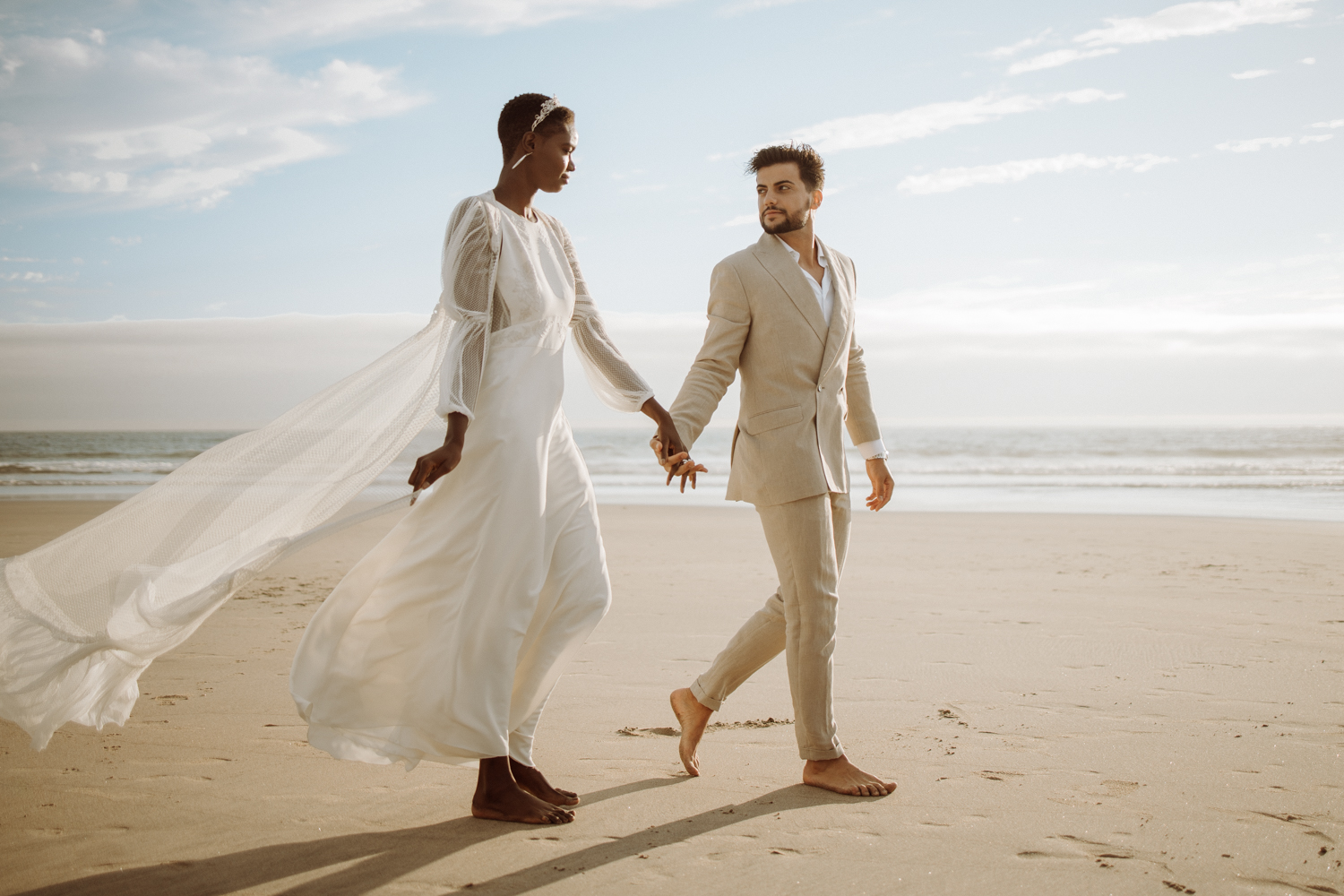 A wedding couple holds hands and walks along the beach.