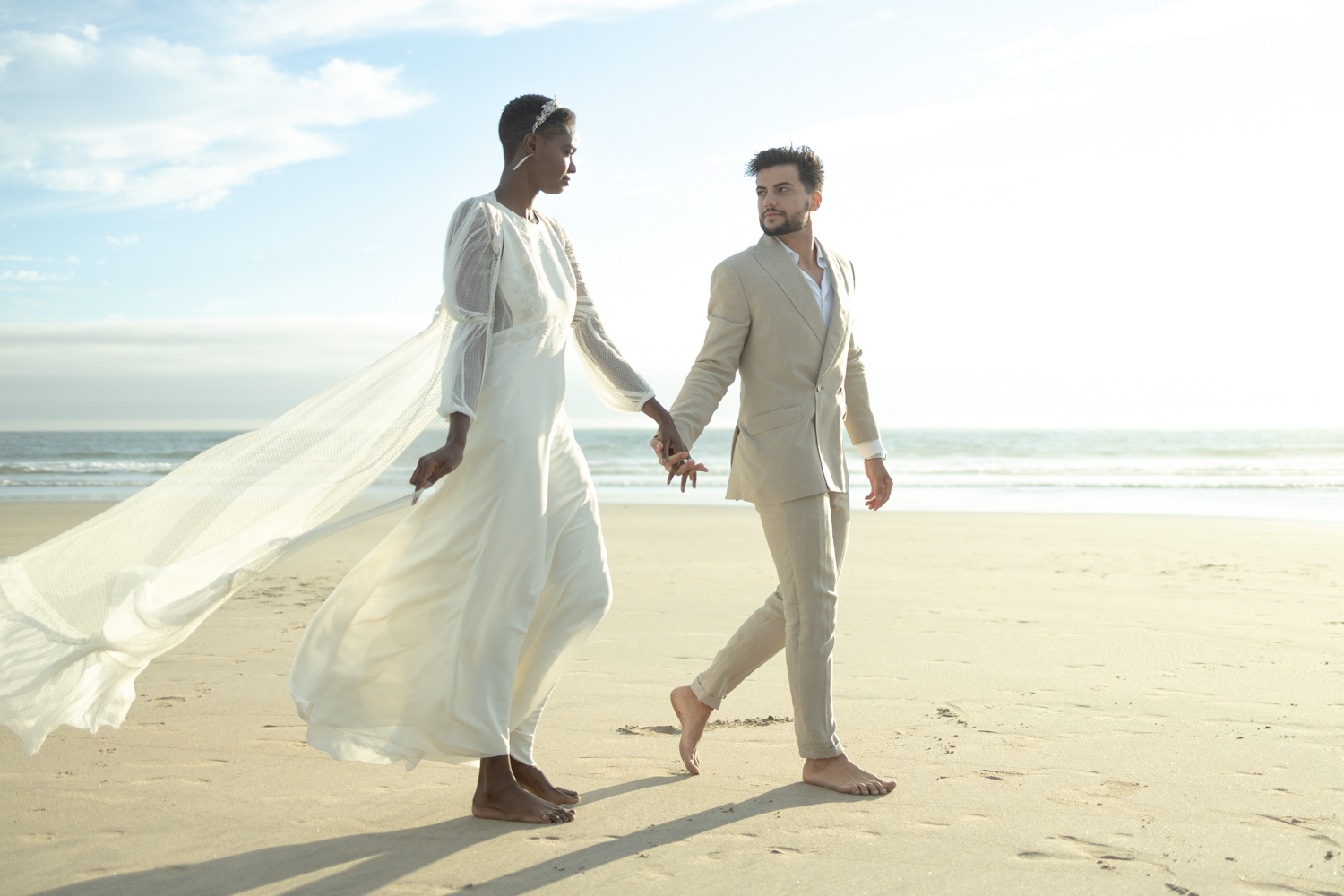 An unedited photo of a wedding couple that holds hands and walks along the beach.