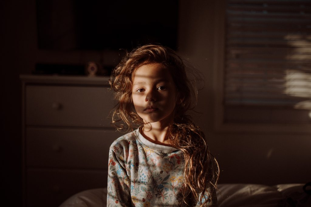 A portrait of a kid that sits on a bed in her room.