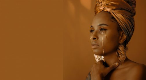 A closeup of a woman crying golden tears and looking into the distance.