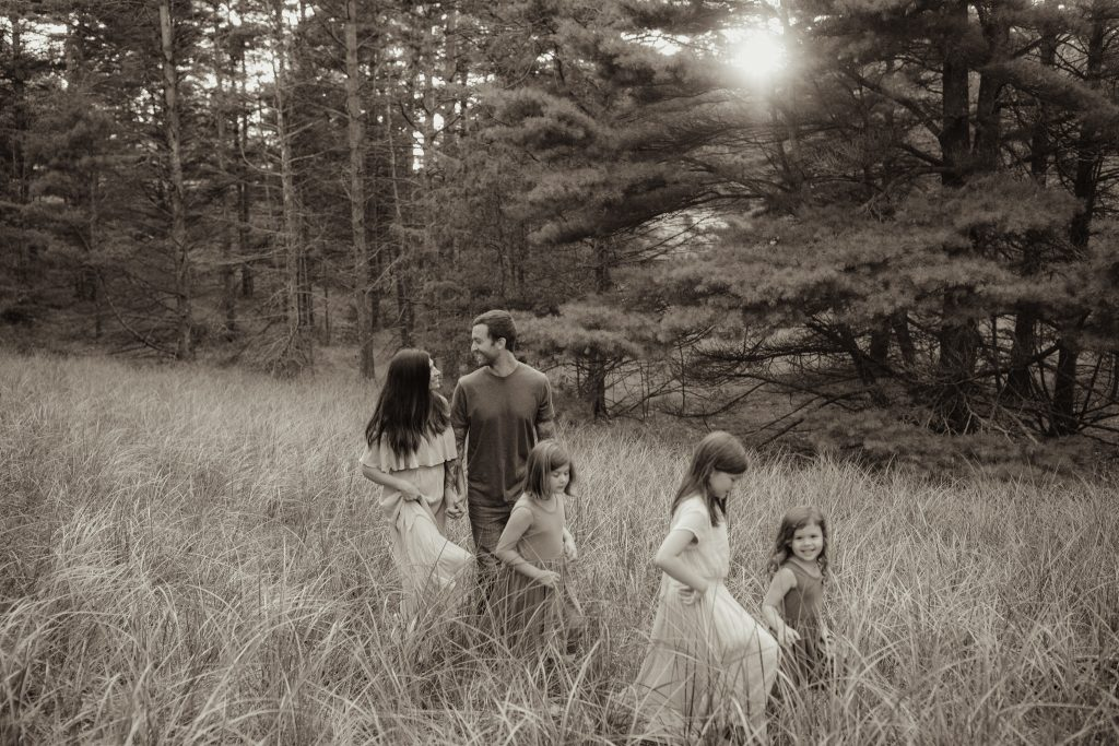 A couple and their three children are walking through the meadow.