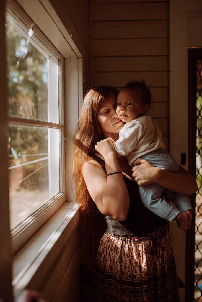 A mother cuddles her baby while it's looking outside of the window.