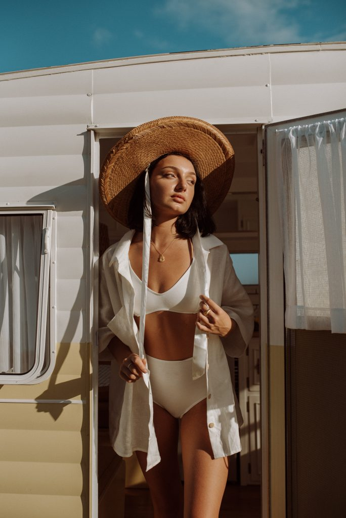 A portrait of a woman who stands at the door of a camper.