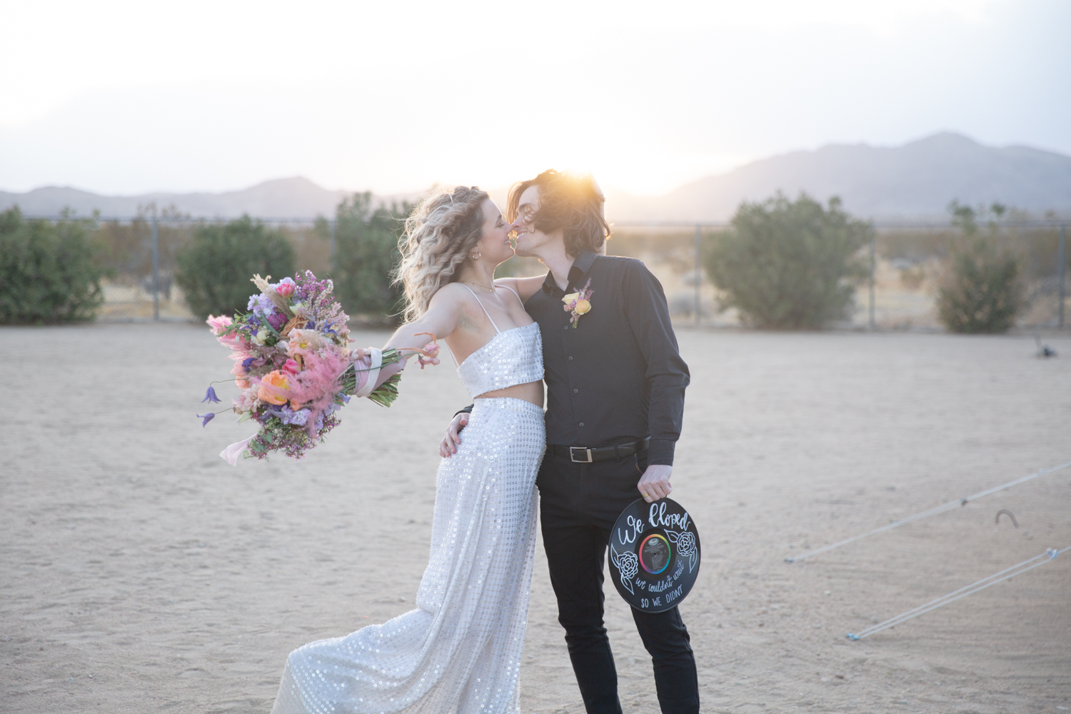 An unedited photo of a wedding couple that kisses each other, and the bride throws her bridal bouquet around.