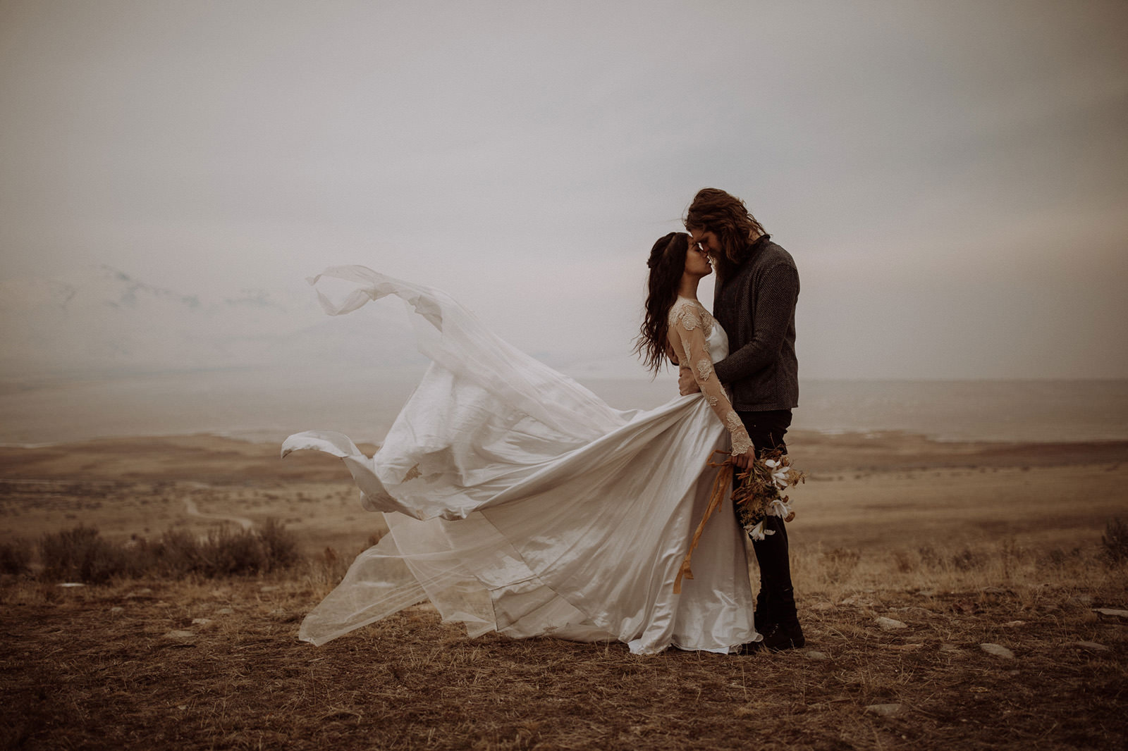 A wedding couple stands on a field on a windy day, and it looks like her dress is about to fly away.