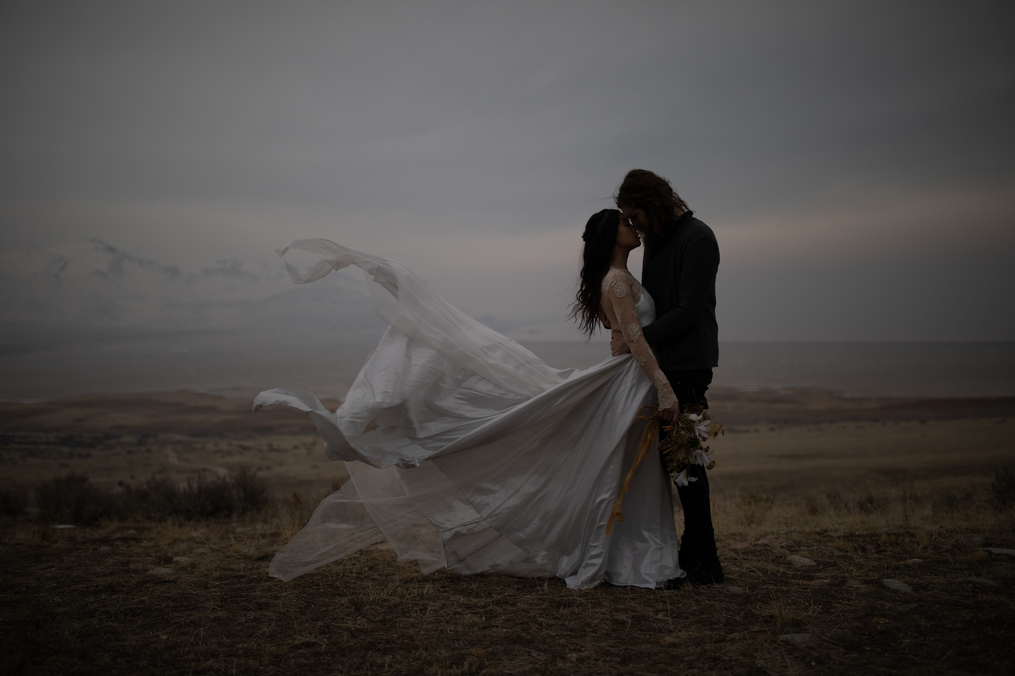 An unedited photo of a wedding couple that stands on a field on a windy day, and it looks like her dress is about to fly away.