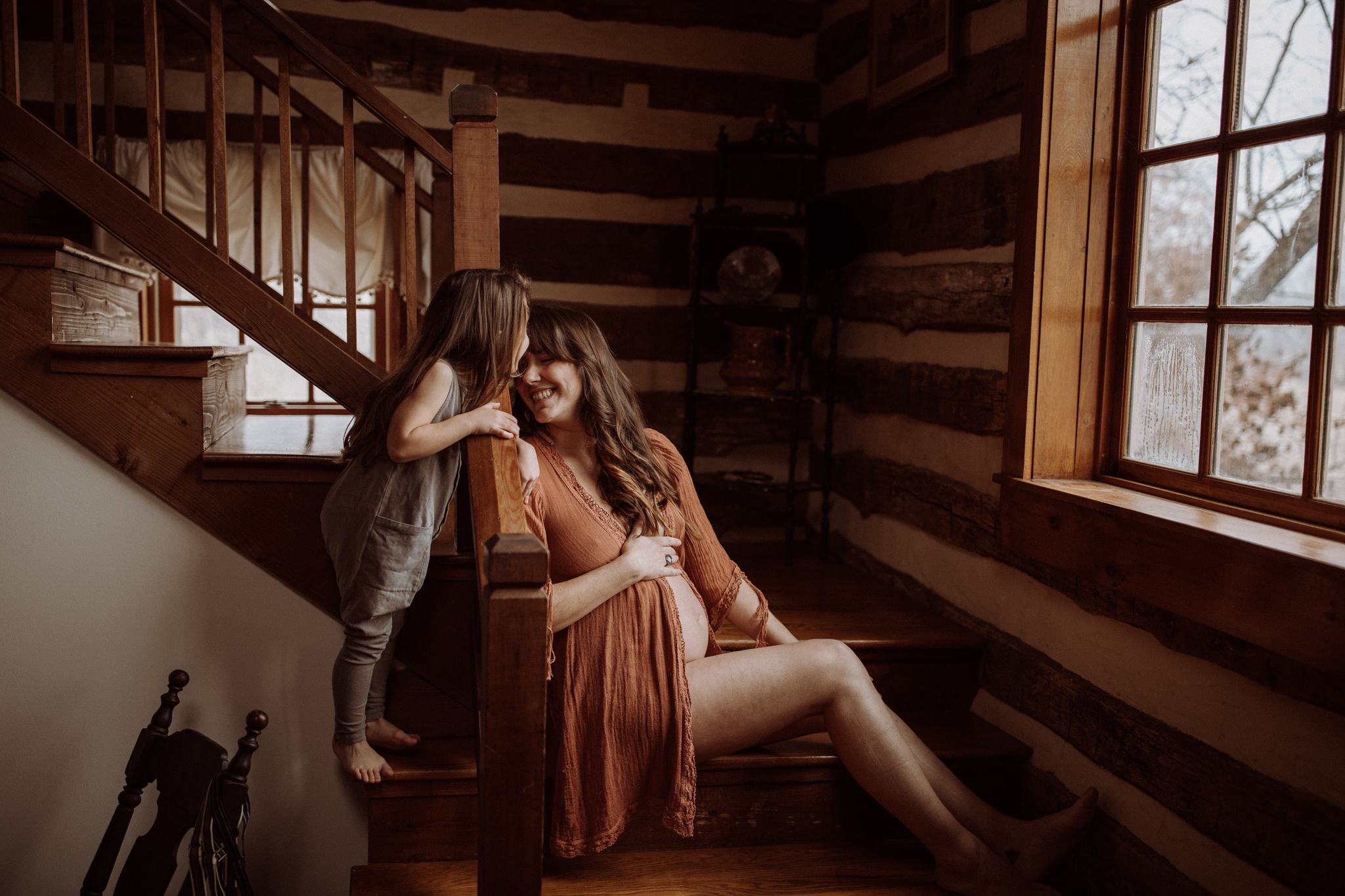 A photo of a pregnant mom who sits on wooden stairs and gets a kiss from a kid.