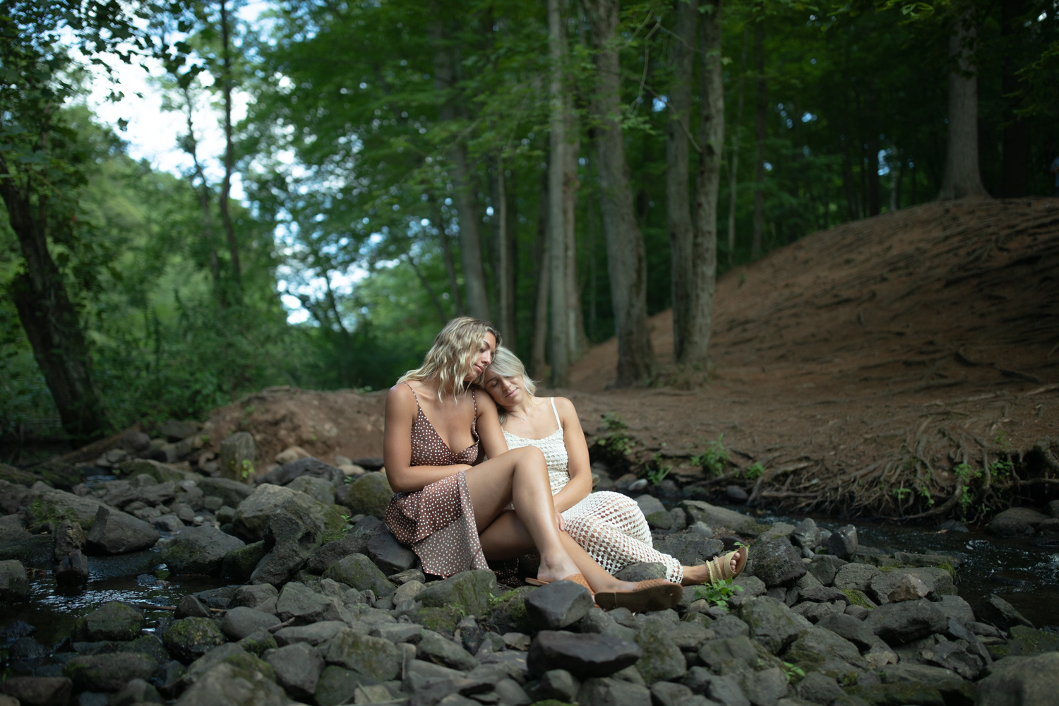 An unedited photo of a couple that cuddles while sitting on rocks in a forest.