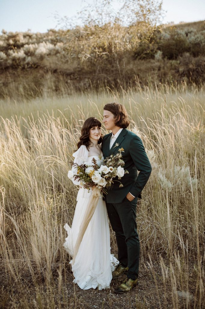 A wedding couple stands in a grass field.