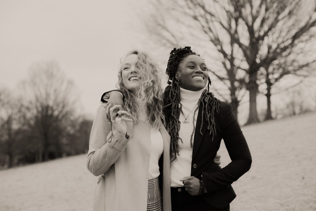 Two women are holding each other, standing in a park and are smiling.