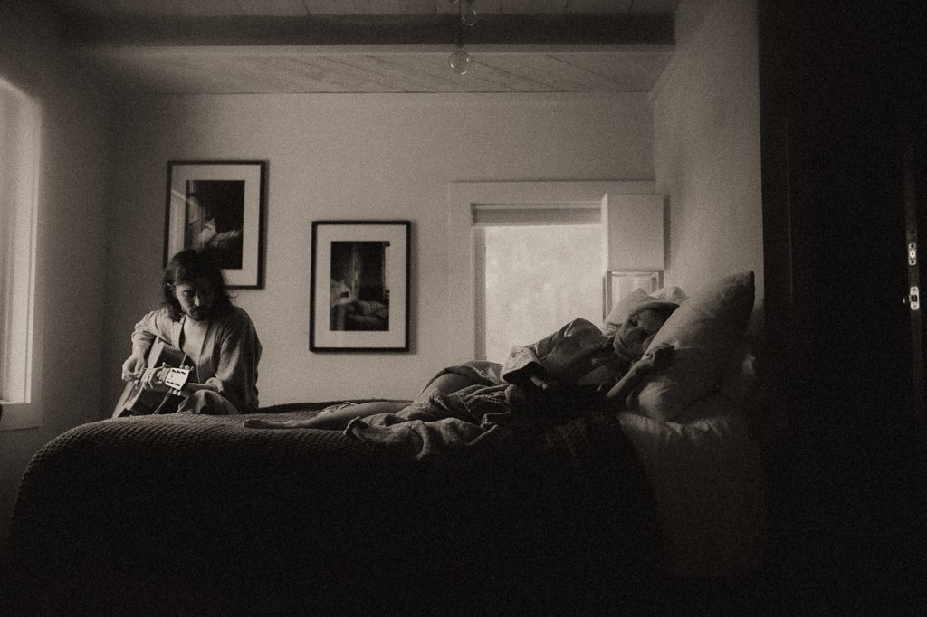 A man is playing guitar and a woman is lying in bed.