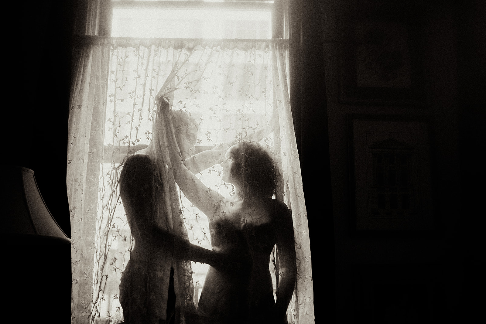 A couple is standing in front of a window and behind curtains.