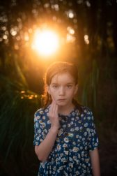 A closeup of a girl standing in the woods with the sunrise in the background.