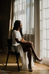 A woman is sitting on a chair and looking out of the window.