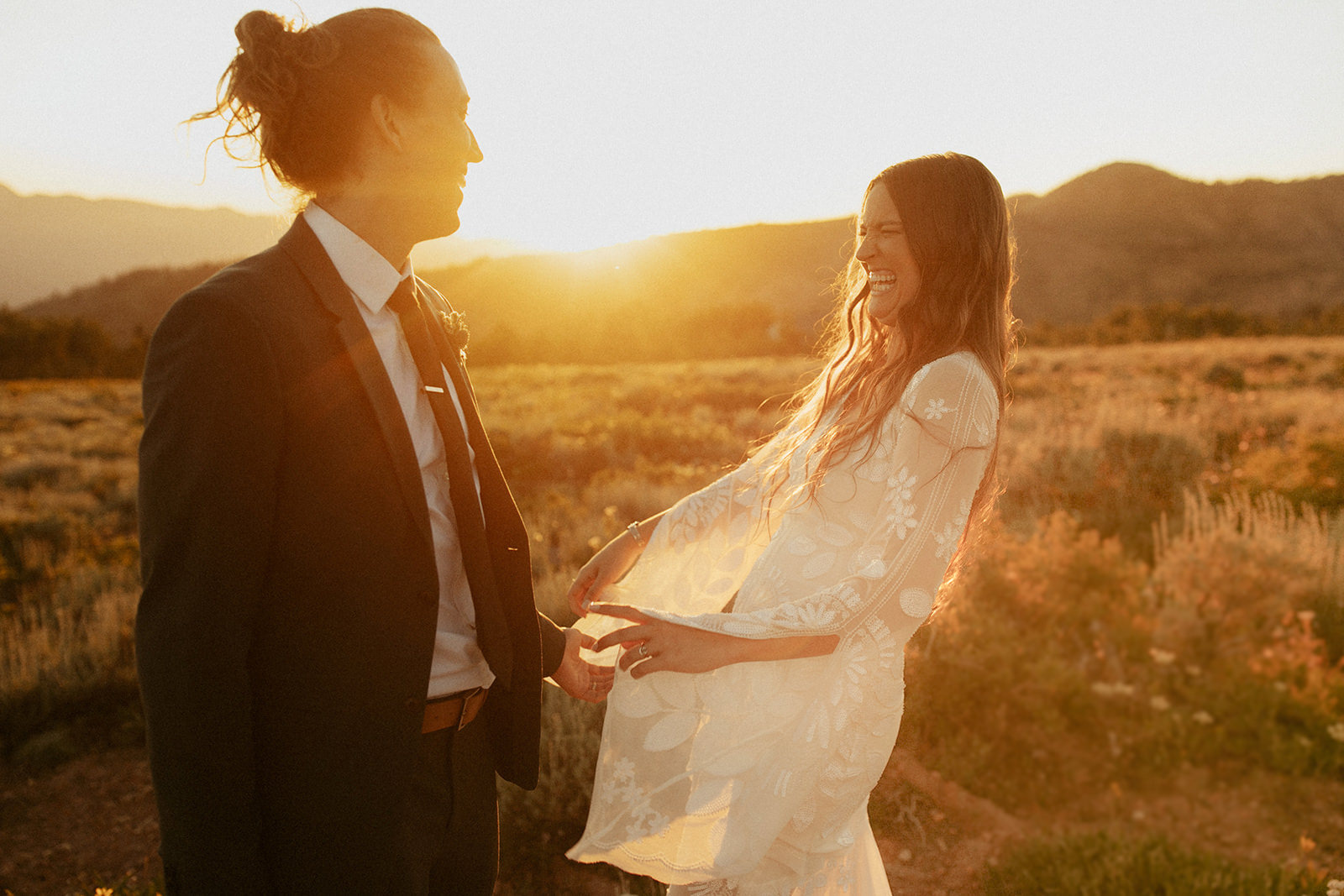 A couple is laughing with each other and standing in front of a meadow and mountains.