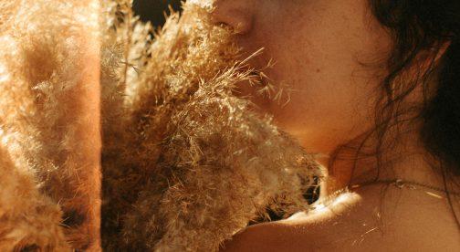 A closeup of a woman holding pampas grass.