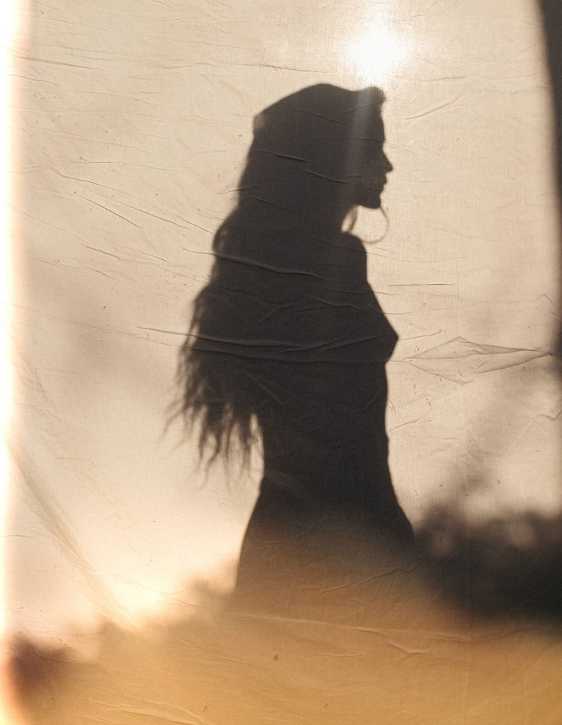 The picture shows a cloth with a shadow of a woman on it.
