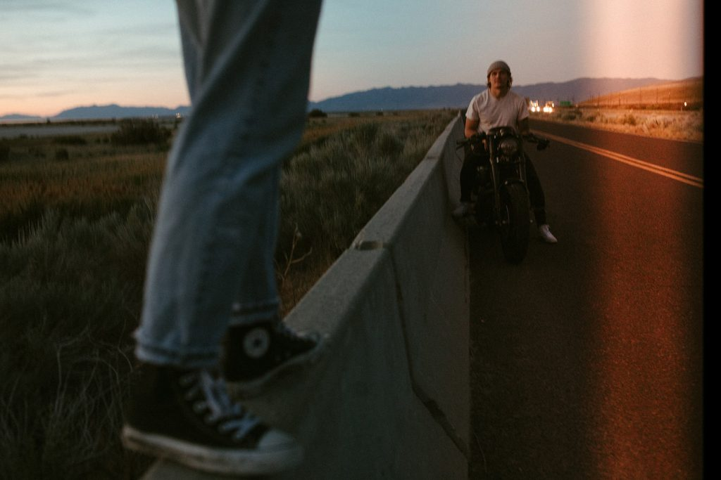 A biker is stopping at the side of the road and another person is walking on a wall that creates the boarder to the road.