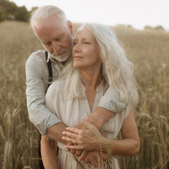Elderly Couple Hugging in a field